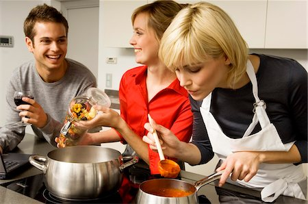 Two young women and a young man preparing food in the kitchen Stock Photo - Premium Royalty-Free, Code: 6108-05861130