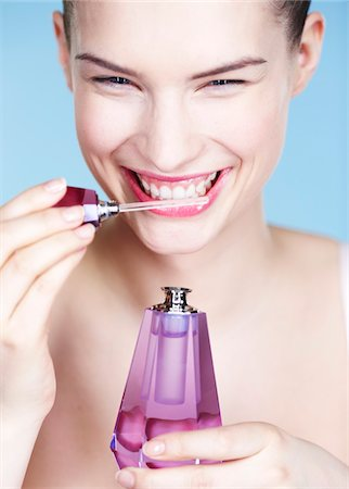 smelly - Young woman smelling perfume Stock Photo - Premium Royalty-Free, Code: 6108-05861326
