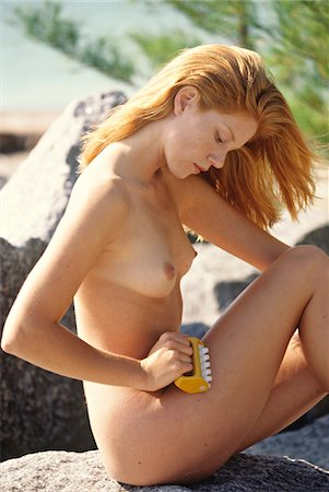 female nud - Naked young woman massaging her thigh, sitting on a rock, seaside Stock Photo - Premium Royalty-Free, Code: 6108-05861595
