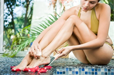 foot massage - Woman rubbing her foot with a pumice stone Stock Photo - Premium Royalty-Free, Code: 6108-05861668