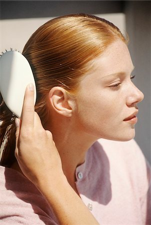 shiny - Young woman brushing her hair, outdoors Stock Photo - Premium Royalty-Free, Code: 6108-05861605