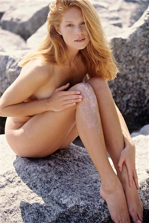Naked young woman applying suncream on her leg, outdoors Stock Photo - Premium Royalty-Free, Code: 6108-05861629