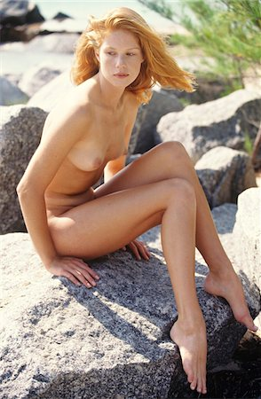 Naked young woman sitting on a rock, outdoors Stock Photo - Premium Royalty-Free, Code: 6108-05861637