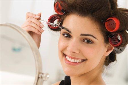 Portrait of a woman tweezing eyebrows Stock Photo - Premium Royalty-Free, Code: 6108-05862275