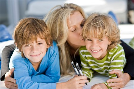 people kissing little boys - Portrait of two boys smiling with their mother Stock Photo - Premium Royalty-Free, Code: 6108-05862755