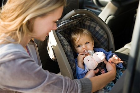 Woman fastening her son on a baby seat in a car Stock Photo - Premium Royalty-Free, Code: 6108-05862804