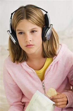 Girl listening to headphones and holding potato chips Stock Photo - Premium Royalty-Free, Code: 6108-05862953