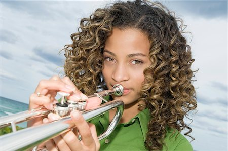 Portrait of a girl playing a trumpet Stock Photo - Premium Royalty-Free, Code: 6108-05862919