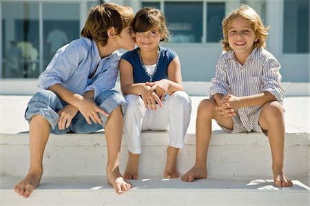 people kissing little boys - Boy kissing a girl with his friend sitting beside them Stock Photo - Premium Royalty-Free, Code: 6108-05863029