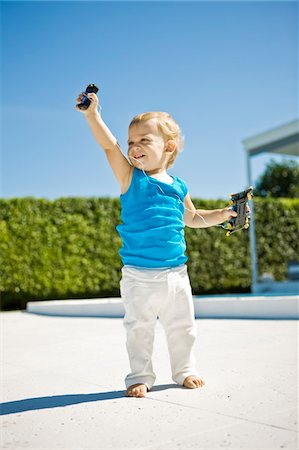 Baby boy holding a remote controlled car and smiling Stock Photo - Premium Royalty-Free, Code: 6108-05863164