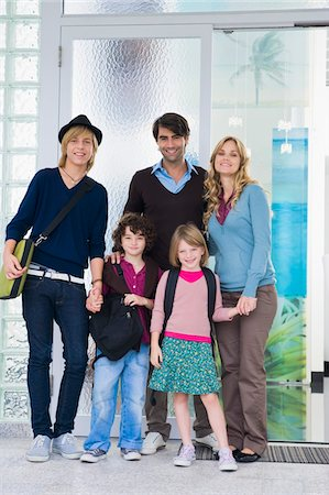 Couple standing with their children and a nanny at the door of a house Stock Photo - Premium Royalty-Free, Code: 6108-05863388