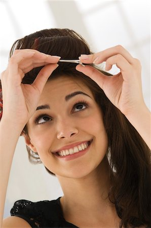 Close-up of a woman removing hair curlers Stock Photo - Premium Royalty-Free, Code: 6108-05863602