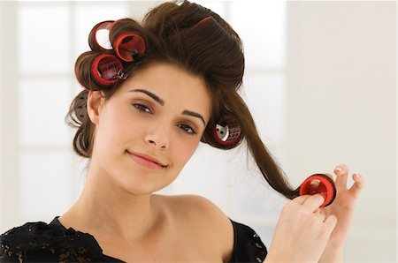 Portrait of a woman removing hair curlers Stock Photo - Premium Royalty-Free, Code: 6108-05863604