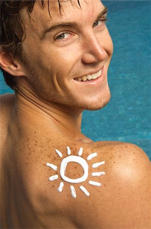 Man with sun shape on his shoulder at the poolside Stock Photo - Premium Royalty-Free, Code: 6108-05863764