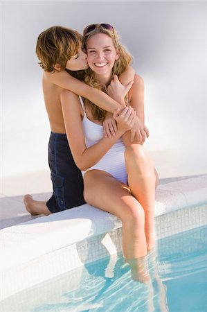 people kissing little boys - Boy hugging his mother at the poolside and smiling Stock Photo - Premium Royalty-Free, Code: 6108-05863793