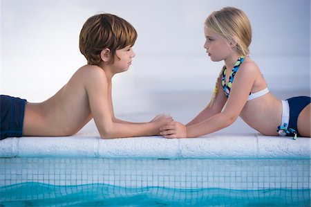 Boy with a girl lying at the poolside Stock Photo - Premium Royalty-Free, Code: 6108-05863846