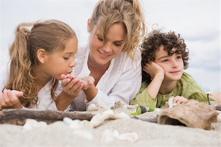 Woman lying with her children on the beach Stock Photo - Premium Royalty-Free, Code: 6108-05864059