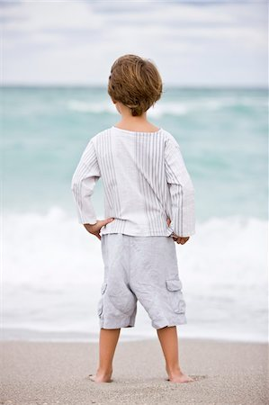 Rear view of a boy standing on the beach Stock Photo - Premium Royalty-Free, Code: 6108-05864109
