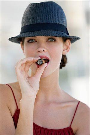 Fashion model smoking a cigar Stock Photo - Premium Royalty-Free, Code: 6108-05864349