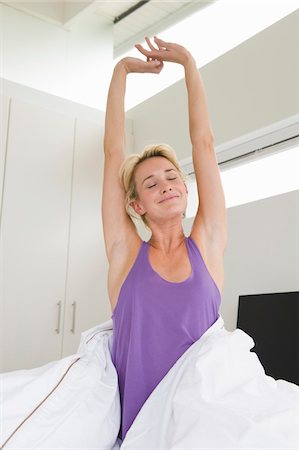 Woman stretching her arms on the bed at morning Stock Photo - Premium Royalty-Free, Code: 6108-05864384
