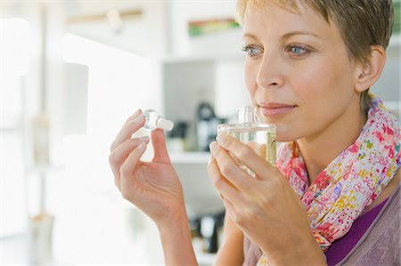 smelly - Woman smelling perfume in a store Stock Photo - Premium Royalty-Free, Code: 6108-05864696