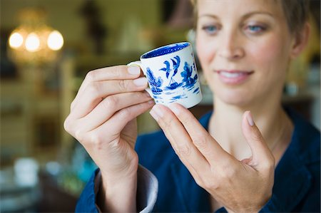 Woman holding a tea cup in a store Stock Photo - Premium Royalty-Free, Code: 6108-05864741