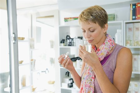 smelly - Woman smelling perfume in a store Stock Photo - Premium Royalty-Free, Code: 6108-05864737