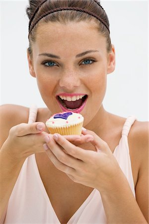 Woman eating a cupcake Stock Photo - Premium Royalty-Free, Code: 6108-05864820