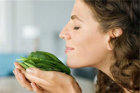 smelly - Woman smelling spinach leaves in the kitchen Stock Photo - Premium Royalty-Free, Code: 6108-05864944