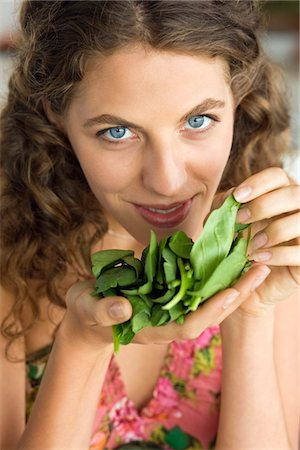 smelly - Woman smelling spinach leaves in the kitchen Stock Photo - Premium Royalty-Free, Code: 6108-05864964