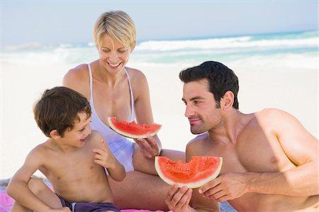 Family enjoying watermelon on the beach Stock Photo - Premium Royalty-Free, Code: 6108-05865140