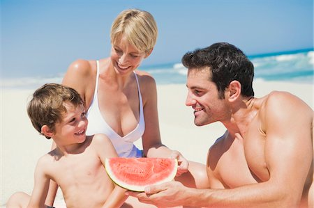 Family enjoying watermelon on the beach Stock Photo - Premium Royalty-Free, Code: 6108-05865167
