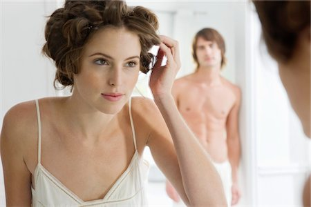 Woman using curlers with her boyfriend in the background Stock Photo - Premium Royalty-Free, Code: 6108-05865499