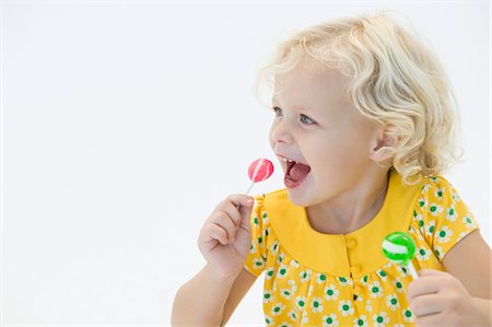 picture of a red lollipop - Girl eating two lollipops Stock Photo - Premium Royalty-Free, Code: 6108-05865568