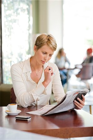 simsearch:6109-08700445,k - Businesswoman sitting in a restaurant and reading a financial newspaper Stock Photo - Premium Royalty-Free, Code: 6108-05865758
