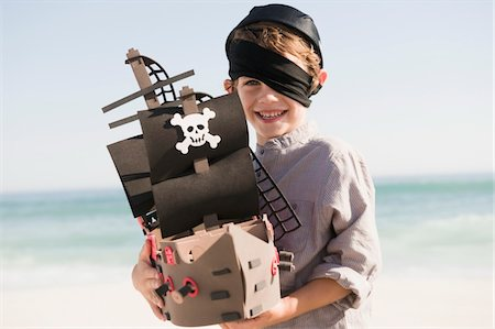 Boy in pirate costume playing with a toy boat Stock Photo - Premium Royalty-Free, Code: 6108-05865942