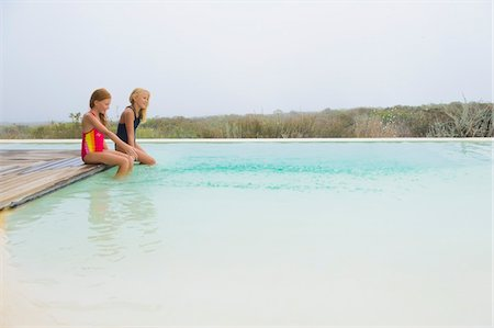 Two girls sitting on a platform at an infinity pool Stock Photo - Premium Royalty-Free, Code: 6108-05865961