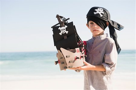 Boy in pirate costume playing with a toy boat Stock Photo - Premium Royalty-Free, Code: 6108-05865967