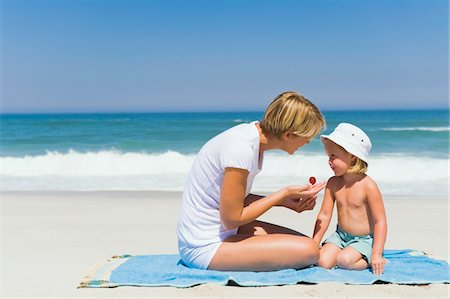 Woman applying suntan lotion on her daughter on the beach Stock Photo - Premium Royalty-Free, Code: 6108-05865975