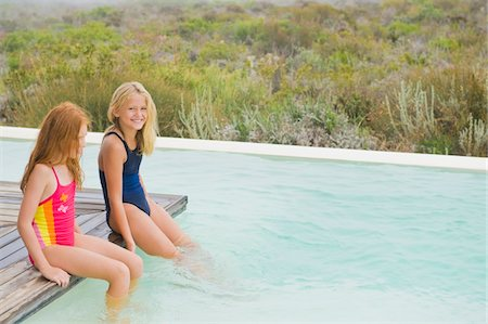 Two girls sitting on a platform at an infinity pool Stock Photo - Premium Royalty-Free, Code: 6108-05865911