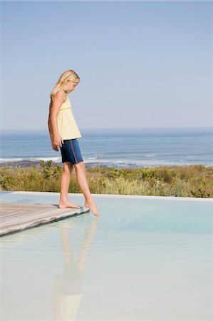 platform - Girl standing on a platform at an infinity pool Stock Photo - Premium Royalty-Free, Code: 6108-05865934