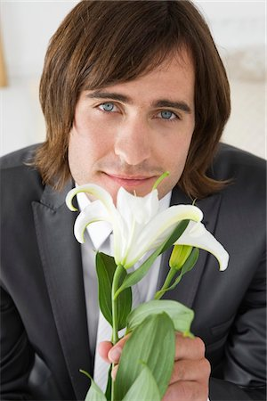smelly - Groom sitting on the bed and holding a lily flower Stock Photo - Premium Royalty-Free, Code: 6108-05866260