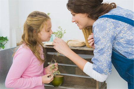 smelly - Woman holding plant with her daughter smelling it Stock Photo - Premium Royalty-Free, Code: 6108-05866330