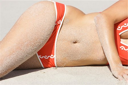 Mid section view of a woman lying on the beach Stock Photo - Premium Royalty-Free, Code: 6108-05866529