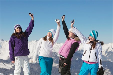 Four teenage girls in ski clothes, with their mobile phones in air Stock Photo - Premium Royalty-Free, Code: 6108-05866977