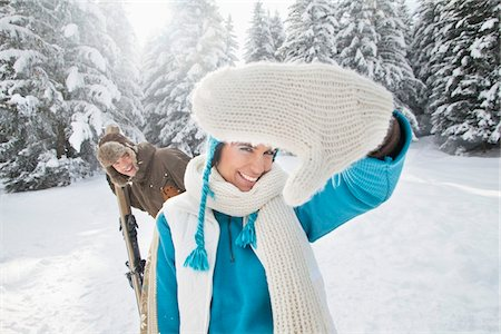 Young woman in winter clothes smiling at camera, man holding skis in background Stock Photo - Premium Royalty-Free, Code: 6108-05867041