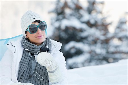 Young woman listening to MP3 player in snow Stock Photo - Premium Royalty-Free, Code: 6108-05867085