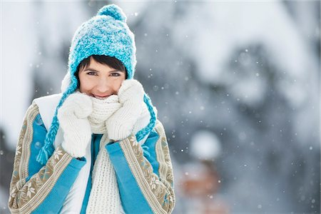Young woman in winter clothes smiling at camera Stock Photo - Premium Royalty-Free, Code: 6108-05867139