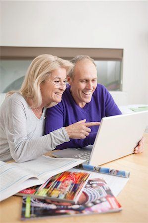 Couple looking at a laptop and smiling Stock Photo - Premium Royalty-Free, Code: 6108-05867315