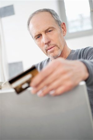 Man doing online shopping with a laptop Stock Photo - Premium Royalty-Free, Code: 6108-05867328